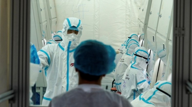 Staff members in protective suits work inside a mobile laboratory for nucleic acid testing, at a sports centre in Beijing